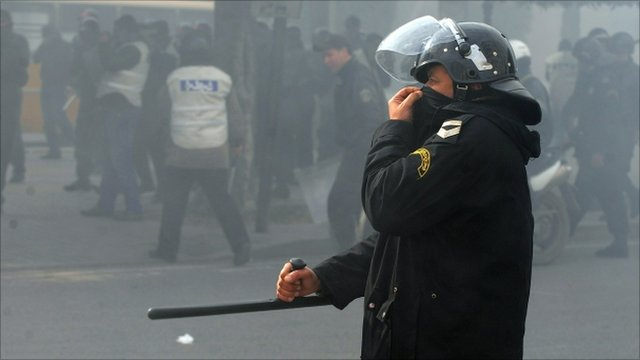 A Tunisian policeman covers his face as riot police fire tear gas during a protest