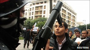 A protester faces up to a policeman in Tunis, 18 January 2011