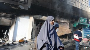 Women walk in front of a burnt mall on 13 January 2011 in a district of Tunis where rioters burnt vehicles and attacked government offices