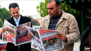 Tunisian men read newspapers on 18 January 2011 at the Kasbah in Tunis