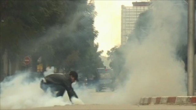 Protestor trying to pick up tear gas canister