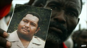 A supporter holds a picture of Jean-Claude Duvalier
