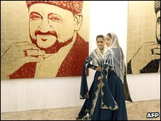 Chechen girls in traditional dress in front of portraits of former President Akhmed Kadyrov