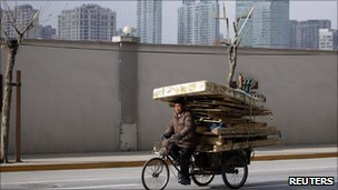 A man rides a tricycle cart past high-rises in Shanghai on 10 Jan 2011