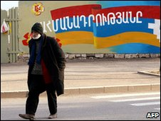 Man walks past mural of flag of breakaway Nagorno Karabakh region
