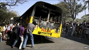 Indian students pull a burnt bus to block the road, during a protest demanding the creation of a separate Telangana state, in Hyderabad, 7 January 2011