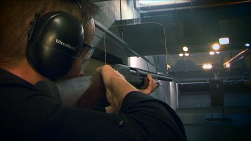 Dan Simmons shooting a shotgun at a hard-drive