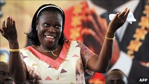 Simone Gbagbo, the wife of incumbent Ivorian president Laurent Gbagbo, dances under a portrait of her husband, during a meeting in his support on 15 January 2011