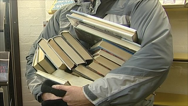 Man holding about a dozen books in his hands