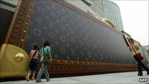 Shoppers walk beside a giant Louis Vuitton advertisement shaped like a briefcase