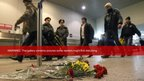 Passengers walk past flowers left on a floor in memory of those killed in Monday's blast at Moscow's Domodedovo airport 25/01