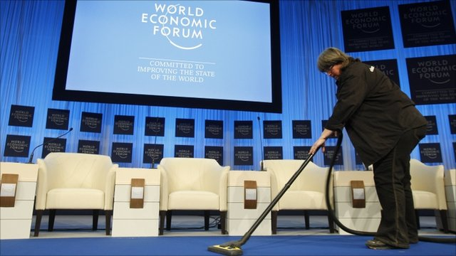 A cleaner vacuums the platform of the main meeting hall at the World Economic Forum in Davos, Switzerland