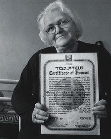 Bahrije Borici holds the Certificate of Honour awarded to her family