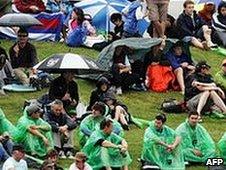 Spectators wait in the rain
