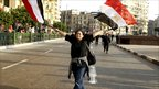 An anti-government protester waves Egyptian flags during clashes with police in downtown Cairo January 25, 2011.