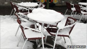 Snow on tables outside a closed cafe