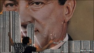 Poster of President Mubarak being torn down by protester.