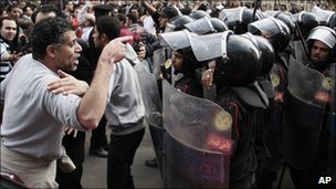 Demonstrator confronts riot police.
