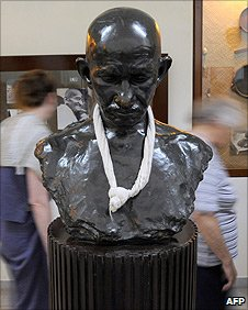 Tourists walk past a bust of Gandhi in Mani Bhavan