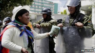 Indigenous woman offering coca leaf to riot police in La Paz