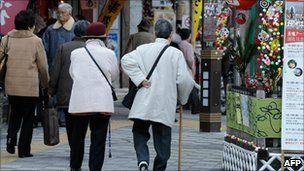 File image of two elderly women walking along a street in Tokyo on 21 December 2010