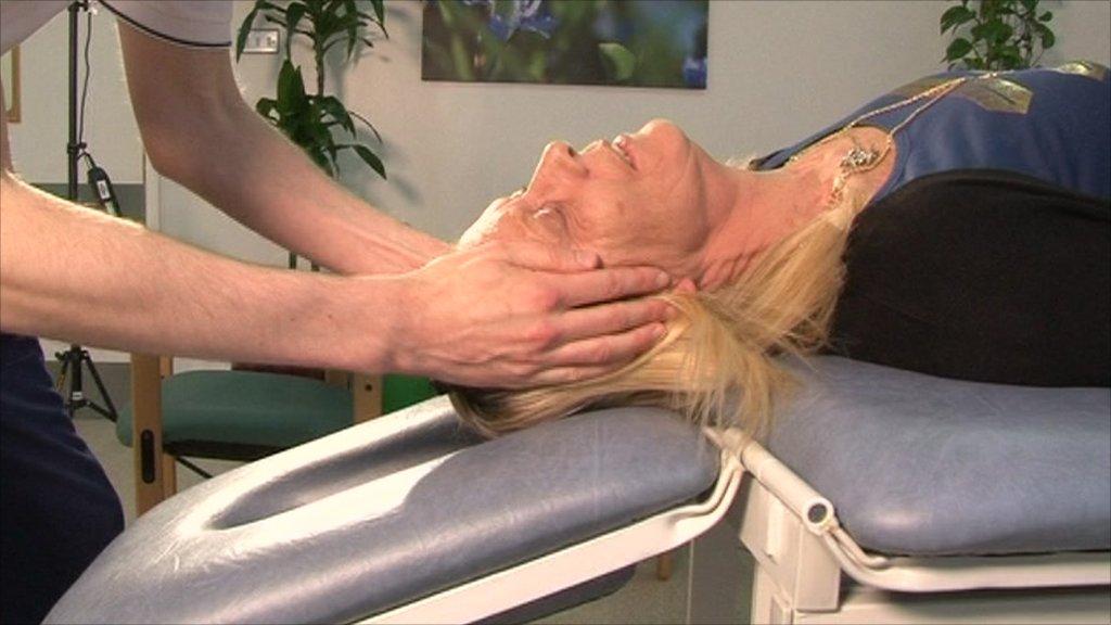Physiotherapist manoeuvres a vertigo sufferer's head