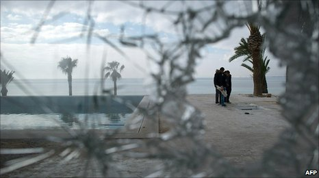 People standing next to the swimming pool at a looted house belonging to one of President Zine al-Abidine Ben Ali's nephews, 19 January 2010