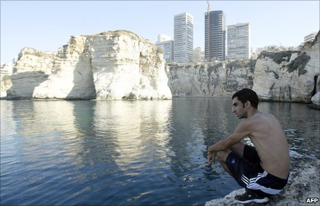 A man sits on rocks and looks out to sea in Beirut