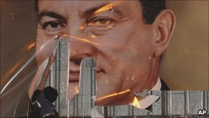 Protester tears poster of Hosni Mubarak
