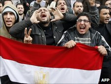 Egyptian demonstrators in Cairo hold the national flag