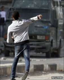 A protester fires a rock at police in Cairo