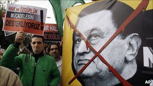 Protesters in Istanbul hold a poster showing the image of President Hosni Mubarak, 28 February 2011