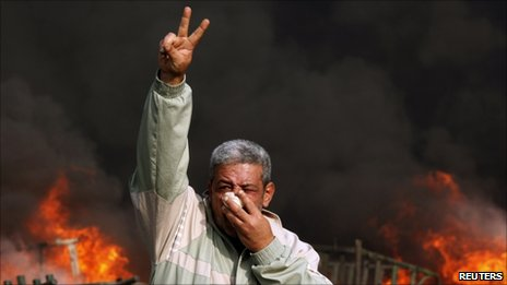 A protester gestures in front of a burning barricade during a demonstration in Cairo. Photo: 28 January 2011