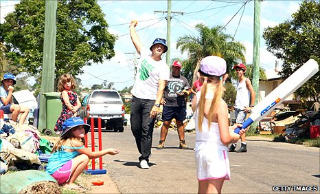 Shane Watson bowls to some children in a game of street cricket