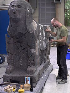 Restorer using glue to stick the statue together