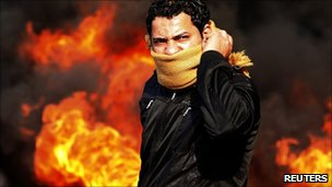 A protester stands in front of a burning barricade during a demonstration in Cairo. Photo: 28 January 2011