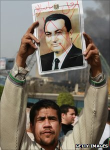 A protester in Tahrir Square holds a photo showing President Mubarak's face crossed out, 29 January