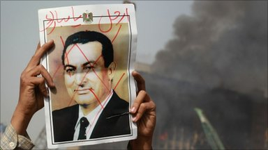 Man holds poster of Hosni Mubarak in front of a burning building, Cairo (29 Jan)