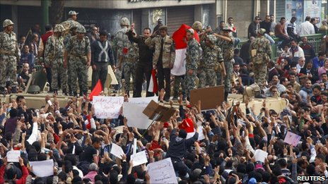 An Egyptian army officer salutes protesters from atop an army armoured personnel carrier in Tahrir square in Cairo, 29 January