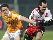 Antrim's Mark Sweeney attempts to halt the run of Michael Drumm at Celtic Park