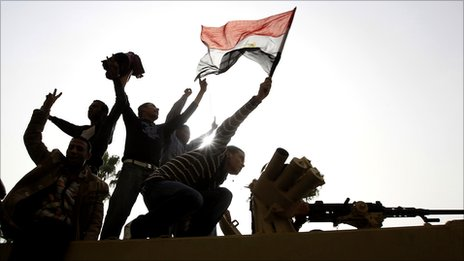 Men stand on top of an armoured Egyptian Army vehicle during a protest in Cairo, 29 January 2011