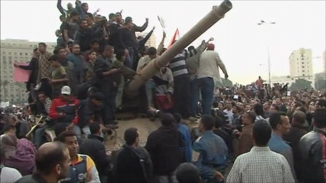 Egyptian protesters surround a tank