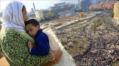A mother hugs her child as she watches protesters in Cairo's Tahrir Square. Photo: 30 January 2011
