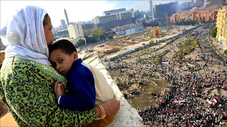 An Egyptian woman holds a child as she watches Egyptian protesters gather at Tahrir square in Cairo, Egypt, 30 January 2011