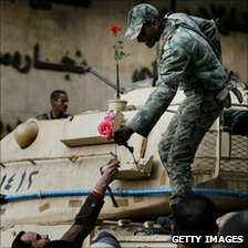 An Egyptian soldier is a handed a flower by an anti-government protesters in Tahrir Square, Cairo, Egypt, 30 January 2011