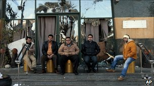 Egyptian men guard the entrance of the Arcadia shopping centre, that has already been partially looted and damaged, Cairo, Egypt, 30 January 2011