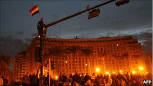 An Egyptian demonstrator sits on top of a set of traffic lights in Tahrir Square in central in Cairo, 30 January 2011