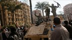 Army soldiers drive an armoured personnel carrier slowly through throngs of anti-government protesters in Tahrir Square