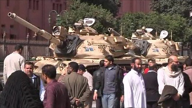 Crowds stand by tanks in Tahrir Square