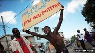 """Protester holds sign saying, """"We won""""t wait 25 years to file a complaint"""", Port-au-Prince, 23 January 2011"""